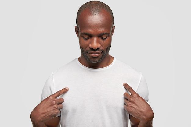 어두운 피부를 가진 아프리카 계 미국인 남성은 흰색 티셔츠에 나타냅니다.