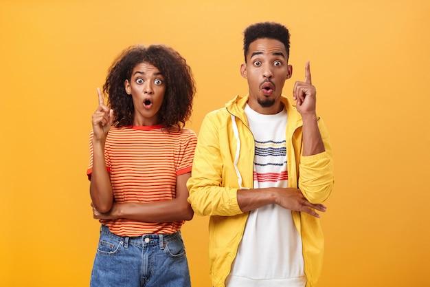 Афро-американский мужчина и женщина поднимают указательные пальцы в жесте эврики, открывая рот