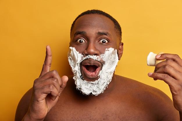 L'uomo afroamericano applica il gel da barba sulle guance