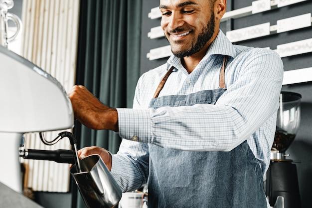 Афро-американский мужчина-бариста готовит кофе на профессиональной кофемашине