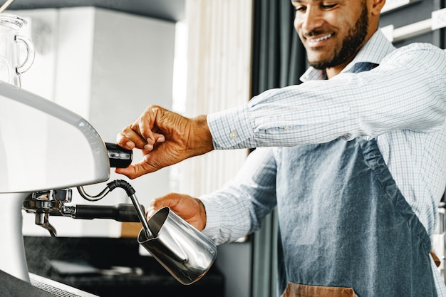 African american man barista preparing coffee on professional coffee machine close up