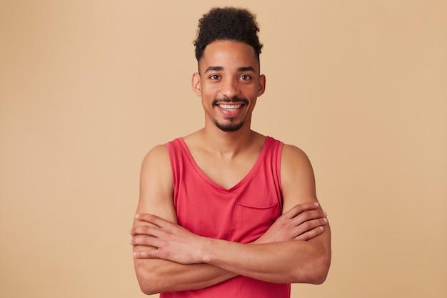 Uomo afroamericano, ragazzo barbuto dall'aspetto felice con acconciatura afro. indossare canottiera rossa. incrocia le mani su una cassa isolata sopra il muro beige pastello