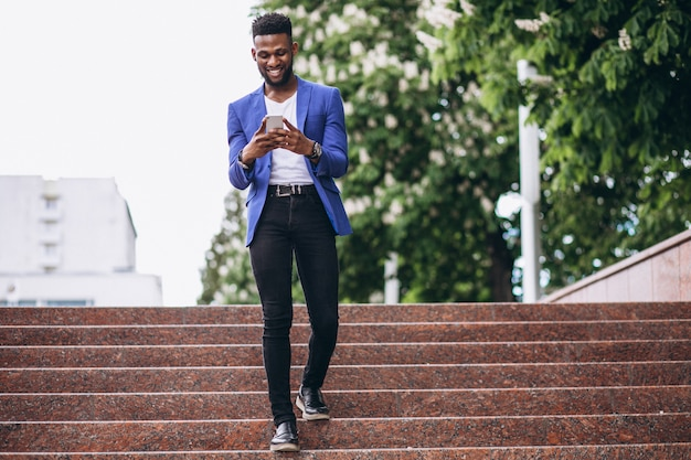 African american man in blue jacket using phone