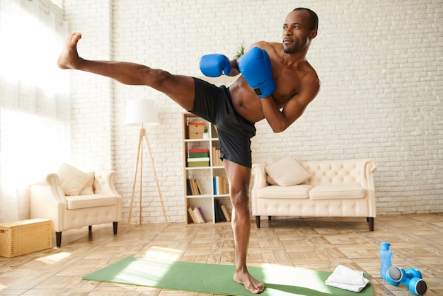African american man in boxing gloves makes kick.