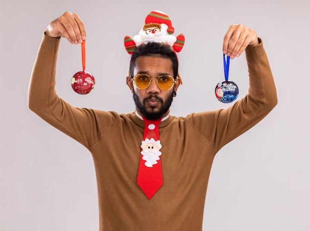 Uomo afroamericano in maglione marrone e orlo di babbo natale sulla testa con cravatta rossa divertente che tiene le palle di natale con espressione confusa in piedi sopra il muro bianco