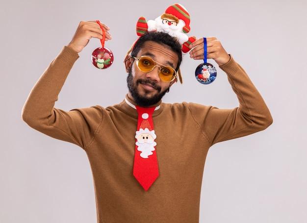 Uomo afroamericano in maglione marrone e orlo di babbo natale sulla testa con cravatta rossa divertente che tiene le palle di natale con il sorriso sul viso in piedi sul muro bianco