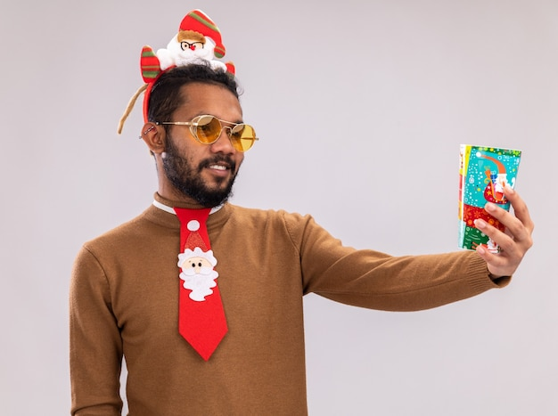 African american man in brown sweater and santa rim on head with funny red tie holding colorful paper cup looking at it with smile on face standing over white background
