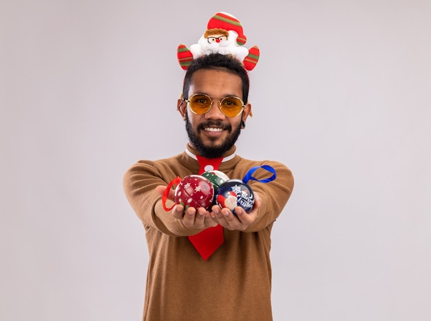 African american man in brown sweater and santa rim on head with funny red tie showing christmas balls looking at camera smiling cheerfully standing over white background