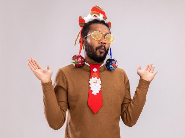 Uomo afroamericano in maglione marrone e orlo di santa sulla testa con cravatta rossa divertente con palle di natale sulle orecchie cercando confuso alzando le braccia in piedi su sfondo bianco