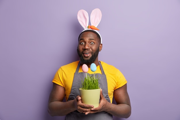 African american man in bunny ears holding easter egg