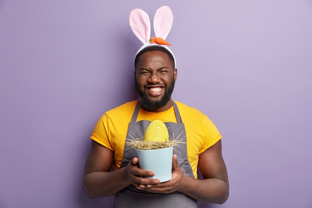 Uomo afroamericano nelle orecchie del coniglietto che tiene l'uovo di pasqua