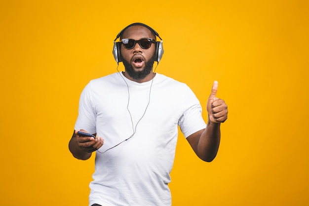 African-american man in casual clothes and headphones listening to music and dancing. thumbs up.