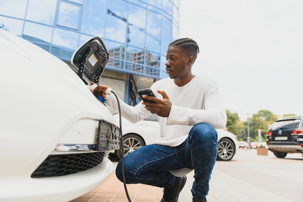 Афро-американский мужчина заряжает свой электромобиль.