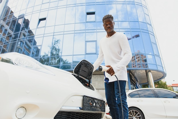 그의 전기 자동차를 충전 하는 아프리카계 미국인 남자.