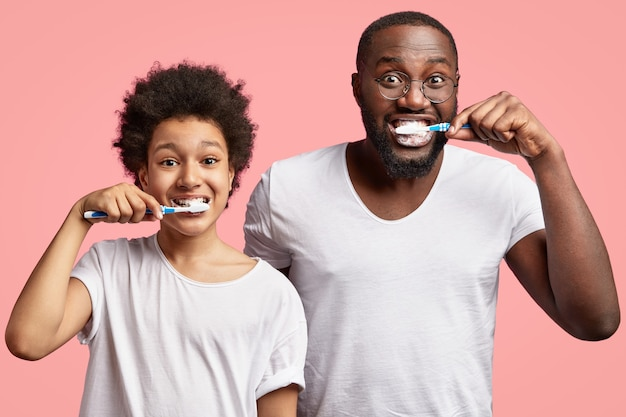 African american man and child brushing teeth
