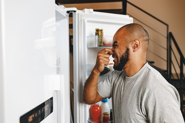 African american man closing nose because of bad smell from fridge