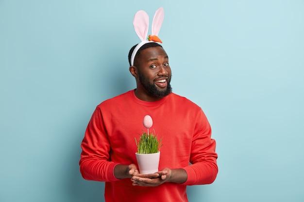 Uomo afroamericano in abiti colorati e orecchie da coniglio