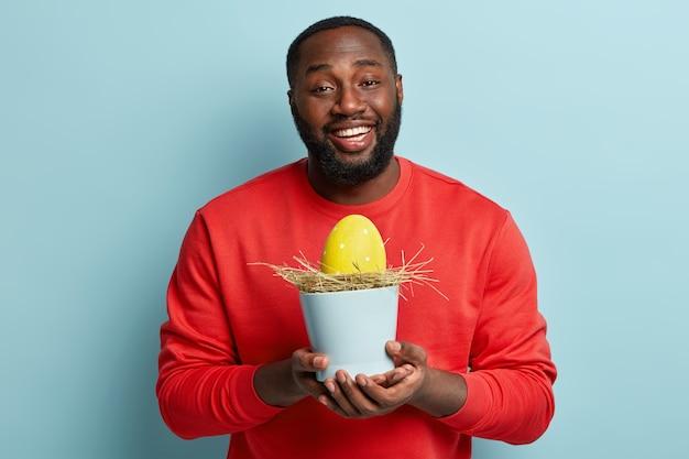 Uomo afroamericano in vestiti variopinti che tengono l'uovo di pasqua