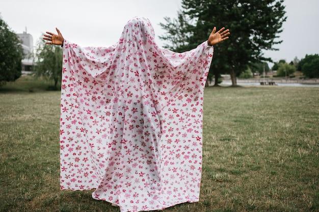 Афро-американский мужчина в призрак костюм позирует открытый в осенний парк.