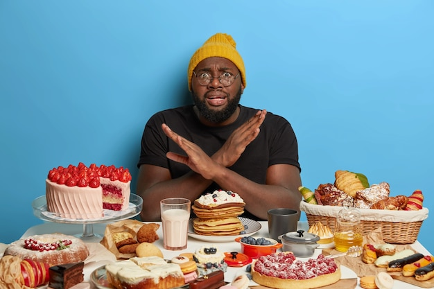 African american man crosses arms over chest, makes denial gesture, refuses eat sugary products, sits at table with bakery, keeps to diet