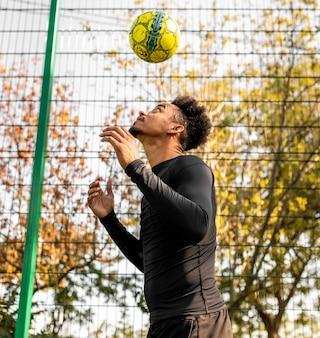 Афро-американский мужчина делает трюки с футбольным мячом