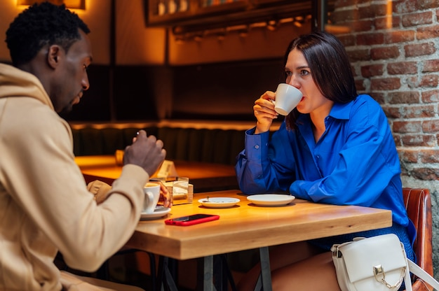 African american man drinking coffee in a coffee shop with a friend