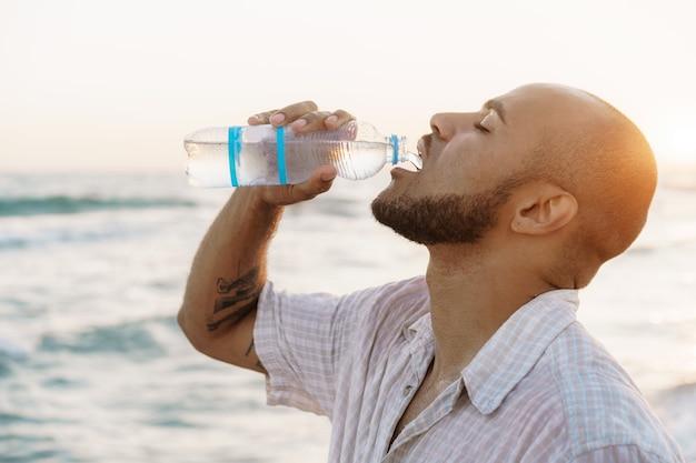 ビーチでボトルから水を飲むアフリカ系アメリカ人の男