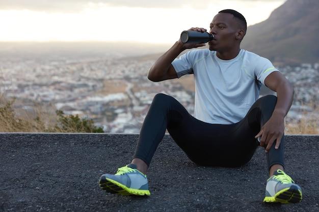 아프리카 계 미국인 남자는 병에서 신선한 물을 마시고, 아스팔트에 앉고, 야외 산에 앉고, 편안한 느낌, 캐주얼 티셔츠, 몰래 바지를 입고 있습니다. 휴식 개념