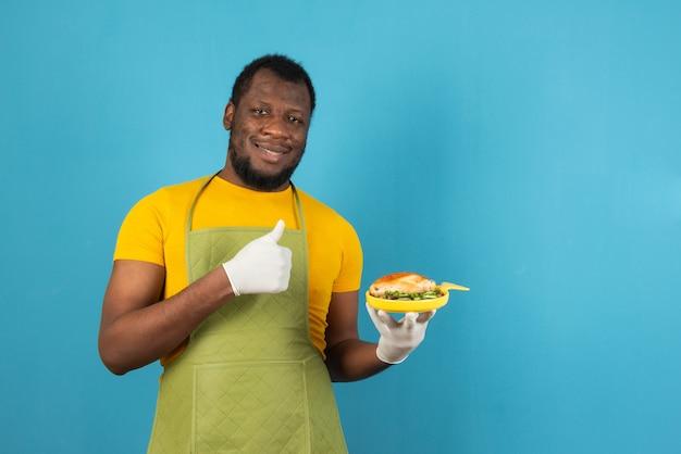 Uomo afroamericano che mangia pasto sorridente felice e positivo, pollice in su facendo segno eccellente e di approvazione, si erge sopra la parete blu chiaro.