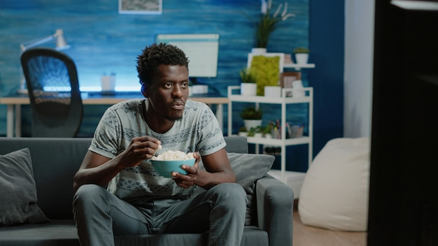 Афро-американский мужчина наслаждается комедией по телевидению