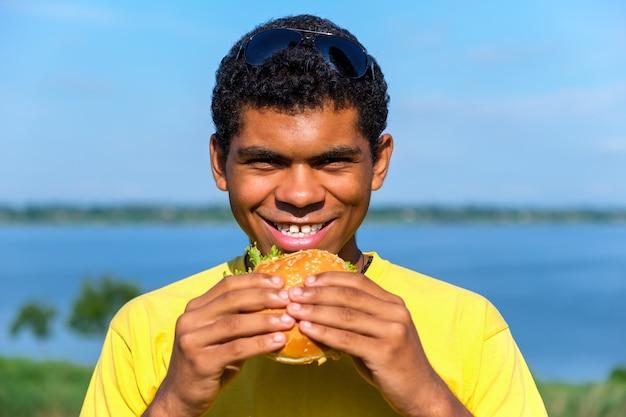 야외에서 햄버거의 맛을 즐기는 아프리카계 미국인 남자