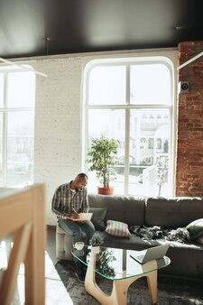 Афро-американский мужчина, фрилансер во время работы в домашнем офисе во время карантина