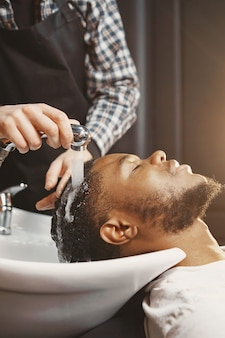 Афро-американский мужчина. парень сидит на стуле. мыть голову.