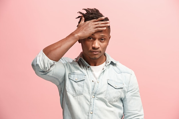 African american man having headache. isolated over pink