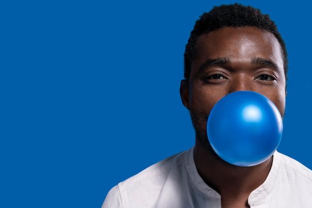 Афро-американский мужчина держит синий воздушный шар