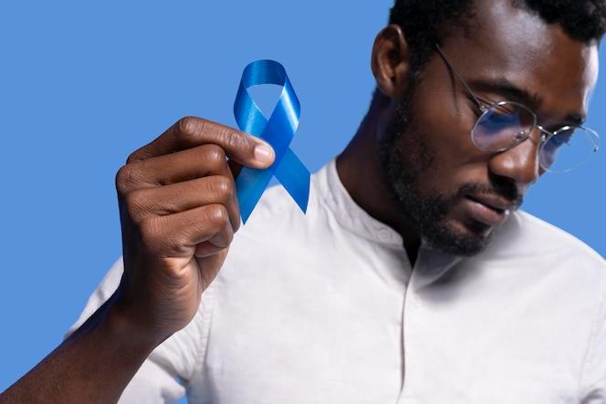青いリボンを持っているアフリカ系アメリカ人の男