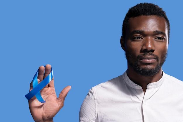 Афро-американский мужчина держит голубую ленту
