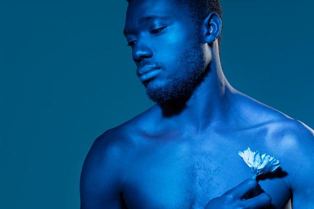 Афро-американский мужчина держит цветок