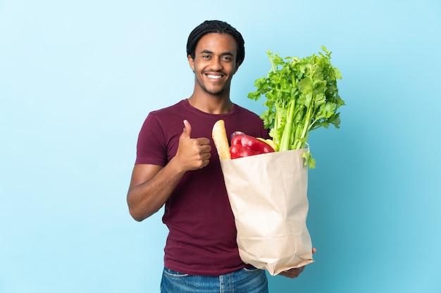 青い背景に分離された食料品の買い物袋を持って親指を立てるジェスチャーを与えるアフリカ系アメリカ人の男