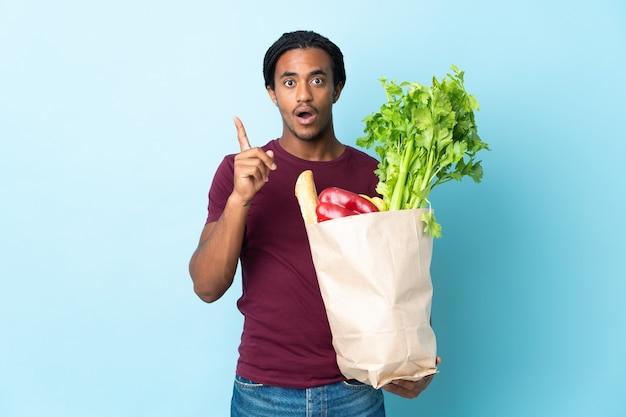 指を持ち上げながら解決策を実現しようと意図して青い背景で隔離の食料品の買い物袋を保持しているアフリカ系アメリカ人の男