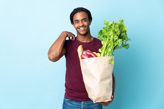笑って青い背景で隔離の食料品の買い物袋を保持しているアフリカ系アメリカ人の男