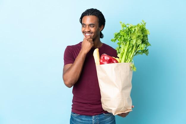 横を見て笑っている青い背景で隔離の食料品の買い物袋を保持しているアフリカ系アメリカ人の男