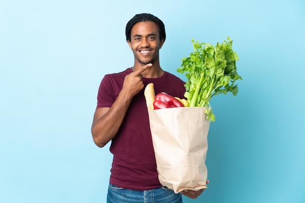 製品を提示する側を指している青い背景で隔離の食料品の買い物袋を保持しているアフリカ系アメリカ人の男
