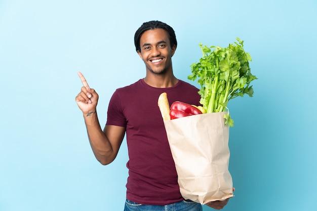 파란색 배경에 고립 된 식료품 쇼핑 가방을 들고 아프리카 계 미국인 남자가 보여주는 최고의 기호에 손가락을 들어 올려