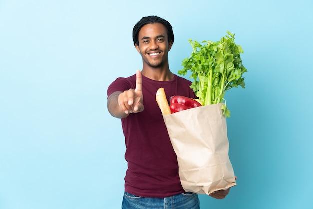 파란색 벽 표시에 고립 된 식료품 쇼핑 가방을 들고 손가락을 들고 아프리카 계 미국인 남자