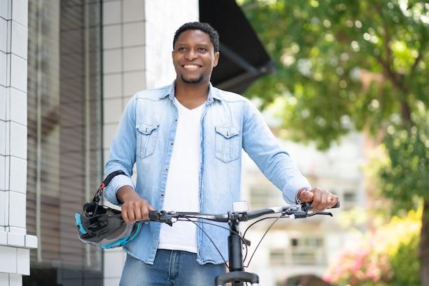 거리에서 자전거와 함께 걷는 동안 그의 손에 헬멧을 들고 아프리카 계 미국인 남자