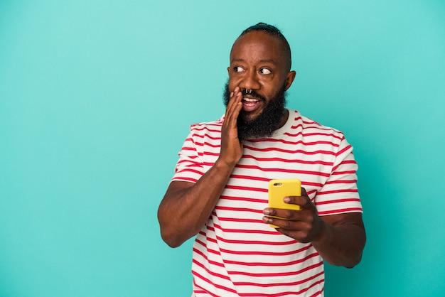 파란색 배경에 격리된 휴대전화를 들고 있는 아프리카계 미국인 남성이 비밀 핫 브레이킹 뉴스를 말하고 옆을 바라보고 있다