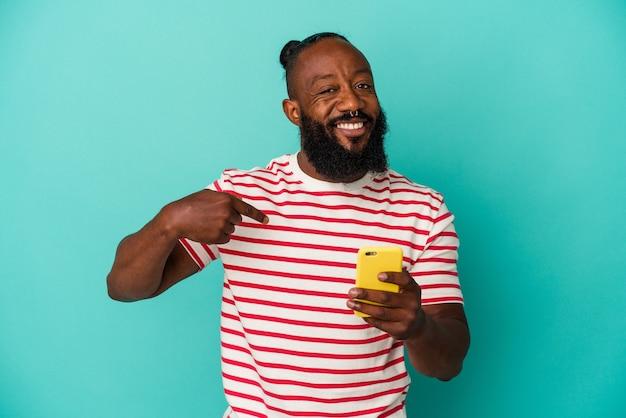 誇りと自信を持って、シャツのコピースペースを手で指している青い背景の人に分離された携帯電話を保持しているアフリカ系アメリカ人の男
