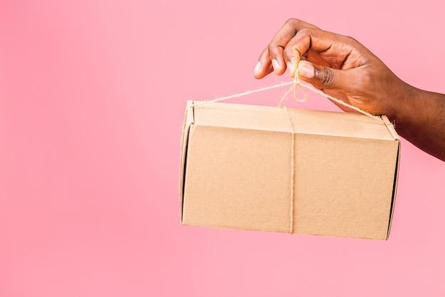 Афро-американский мужчина держит посылку рука держит ящик для доставки