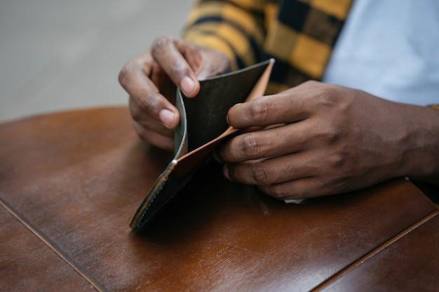 空の財布を持っているアフリカ系アメリカ人の男。お金の概念はありません